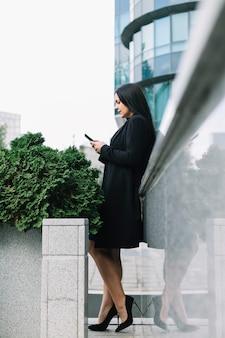 Seitenansicht einer schönen geschäftsfrau, die smartphone hält