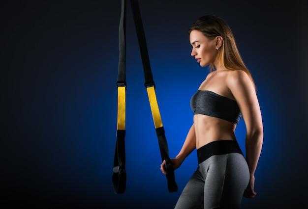 Seitenansicht einer schönen jungen sportlerin, die gegen eine dunkle wand mit hängenden trägern steht. konzept von sportgeräten und fitnesskursen zu hause oder im fitnessstudio