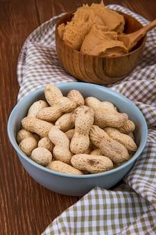 Seitenansicht einer schüssel gefüllt mit erdnüssen in der schale mit erdnussbutter in einer holzschale auf karierter tischdecke