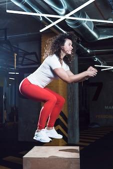 Seitenansicht einer sitzfrau, die springende hocke auf holzkiste tut