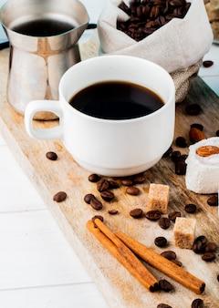 Seitenansicht einer tasse kaffee mit türkischen freuden rahat lokum und verstreuten kaffeebohnen auf rustikalem hintergrund