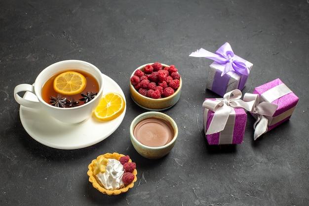 Seitenansicht einer tasse schwarzen tee mit zitrone, serviert mit schokoladenhimbeere und geschenken auf dunklem hintergrund