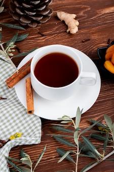 Seitenansicht einer tasse tee mit getrockneten aprikosen und zimtstangen auf holz