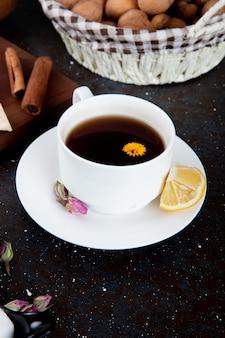 Seitenansicht einer tasse tee mit zitronenscheibe und zimtstange und einem korb mit walnüssen auf schwarz