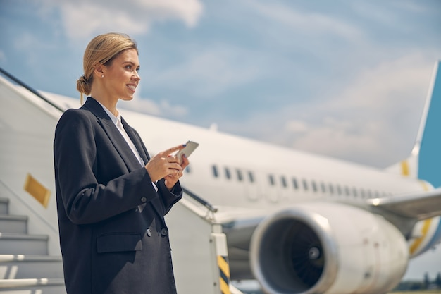 Seitenansicht einer verträumten flughafenangestellten mit einem smartphone, das in die ferne blickt