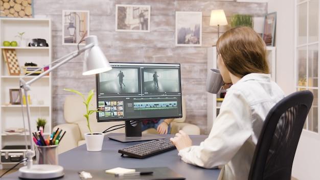 Seitenansicht einer videofilmerin, die von zu hause aus an der postproduktion eines films arbeitet. freund im hintergrund.
