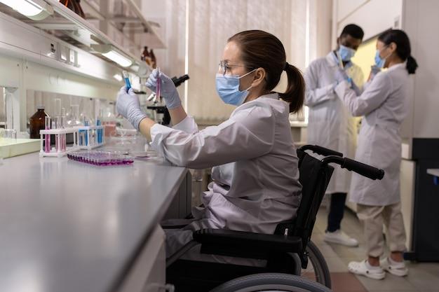 Seitenansicht einer wissenschaftlerin in arbeitskleidung, die flaschen mit flüssigkeiten betrachtet