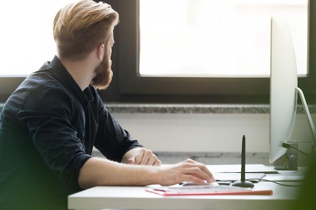 Seitenansicht eines bärtigen jungen mannes, der an seinem schreibtisch sitzt