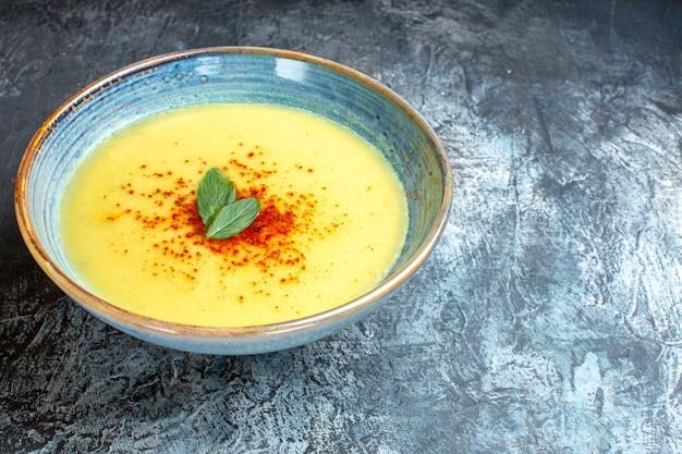 Seitenansicht eines blauen topfes mit leckerer suppe mit minze auf der rechten seite auf blauem tisch