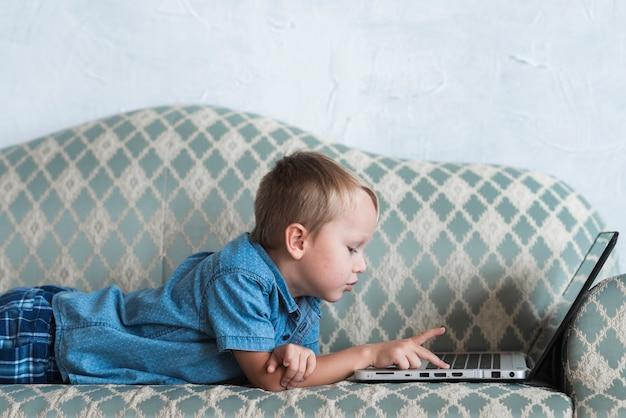 Seitenansicht eines blonden jungen, der auf sofa unter verwendung des laptops liegt