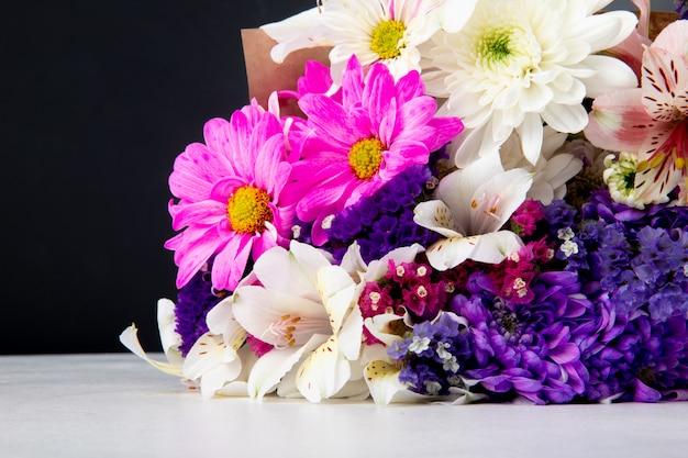 Seitenansicht eines blumenstraußes von rosa weißen und lila farbstatice-alstroemeria- und chrysanthemenblumen in bastelpapier, das auf weißer oberfläche bei schwarzem hintergrund liegt