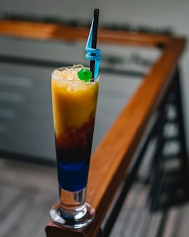 Seitenansicht eines bunten cocktails mit eis und stroh in einem hohen glas auf dunklem hintergrund