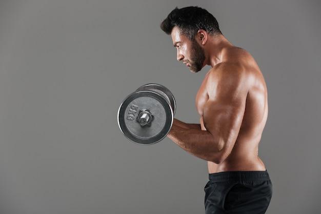 Seitenansicht eines ernsten starken hemdlosen männlichen bodybuilders