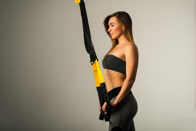 Seitenansicht eines fitnessmodells der schönen jungen frau in sportbekleidung, die mit handaufhängungen auf trägern beschäftigt ist, die im studio auf einer grauen wand aufwerfen