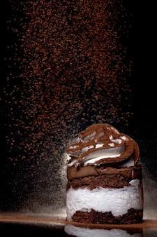 Seitenansicht eines frisch gebackenen schokoladenkuchens, der mit kakao auf arbeitsplatte mit dunklem hintergrund bestreut wird. zurückhaltend. winter essen und trinken konzept. selektiver fokus.