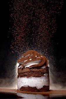Seitenansicht eines frisch gebackenen schokoladenkuchens, der mit kakao auf arbeitsplatte mit dunklem hintergrund bestreut wird