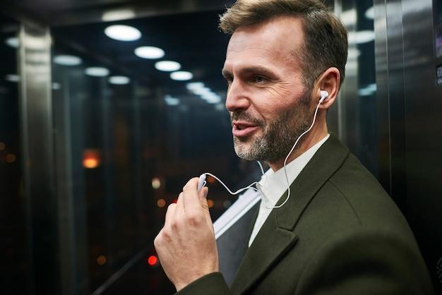 Seitenansicht eines glücklichen geschäftsmannes, der im aufzug musik hört