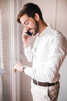 Seitenansicht eines glücklichen jungen geschäftsmannes, der auf mobiltelefon spricht