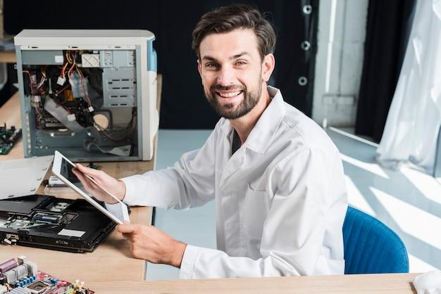 Seitenansicht eines glücklichen männlichen technikers, der digitale tablette in der werkstatt hält