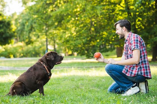 Seitenansicht eines glücklichen mannes, der mit seinem hund spielt