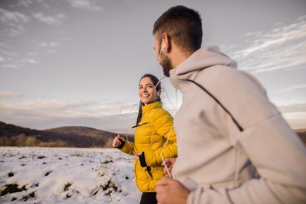 Seitenansicht eines jungen fitnesspaares, das im winter in der natur läuft.