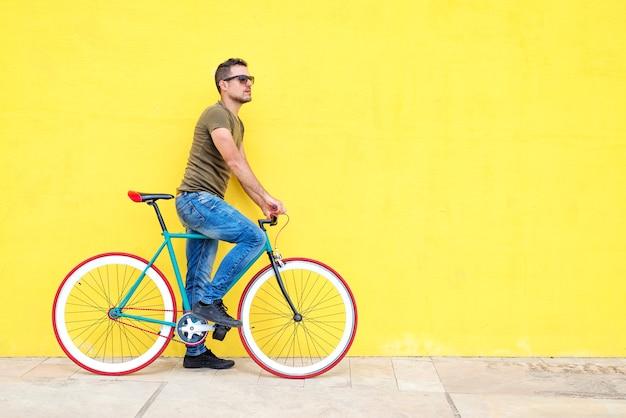 Seitenansicht eines jungen hippie-mannes mit einem festen fahrrad, das zufällige kleidung trägt