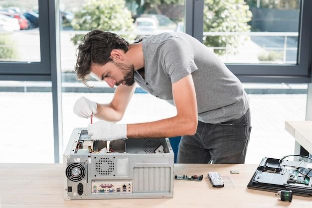 Seitenansicht eines jungen männlichen technikers, der computer in der werkstatt repariert