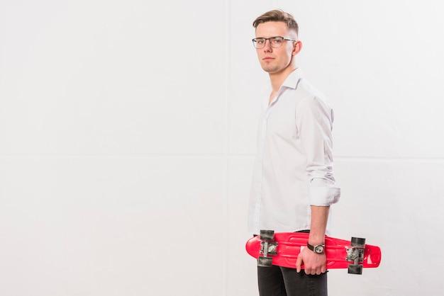 Seitenansicht eines jungen mannes, der gegen die weiße wand hält skateboard steht