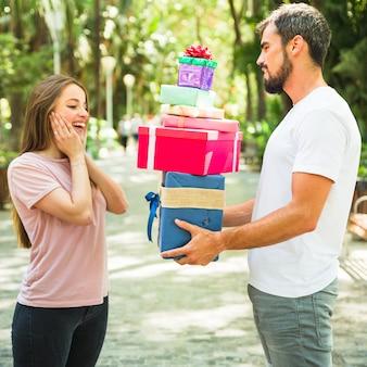 Seitenansicht eines jungen mannes, der seiner überraschten freundin stapel geschenke gibt