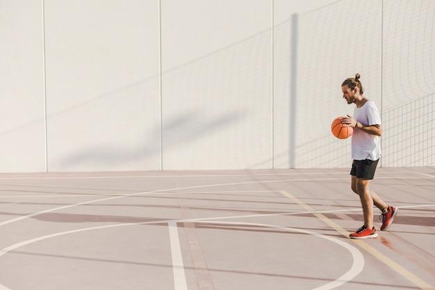 Seitenansicht eines jungen mannes, der vor gericht basketball spielt
