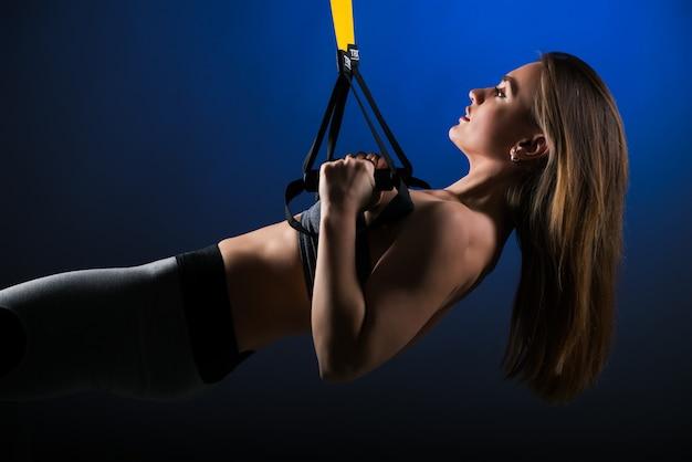 Seitenansicht eines jungen schlanken schönen mädchens in der sportbekleidung, die einen klimmzug an ihren händen unter verwendung der hängenden träger an einer dunkelblauen wand tut. starkes körperkonzept.