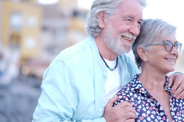 Seitenansicht eines jungen seniorenpaares, das sich im freien bei sonnenuntergang umarmt. kaukasische weißhaarige menschen, die entspannung und freiheit genießen