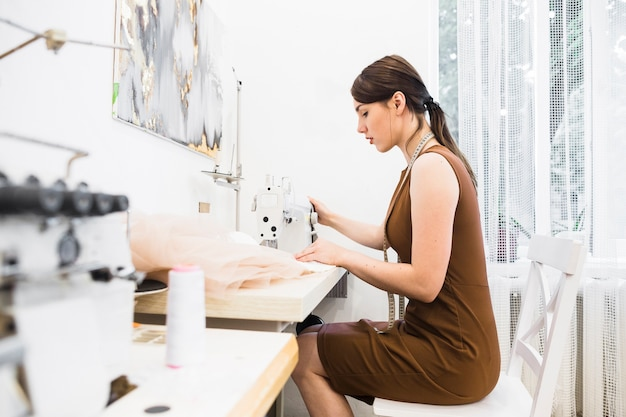 Seitenansicht eines jungen weiblichen designers, der an nähmaschine arbeitet