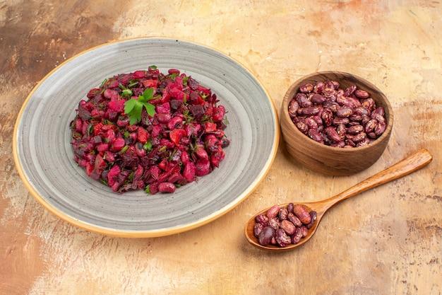 Seitenansicht eines köstlichen salats mit roter beete und bohnen und bohnen innerhalb und außerhalb des topfes auf gemischtem farbtisch