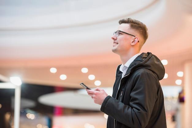 Seitenansicht eines lächelnden jungen mannes, der den handy steht im mall verwendet