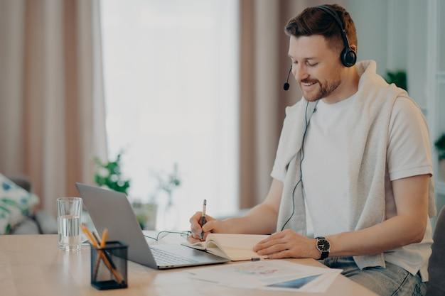 Seitenansicht eines lächelnden mannes im headset, der online-videounterricht hat und während des e-learning zu hause einige notizen im notizbuch schreibt. menschen und fernbildung