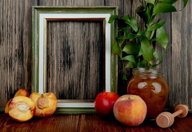 Seitenansicht eines leeren bilderrahmens und frischer reifer pfirsiche mit nektarinen und eines glases mit pfirsichmarmelade auf rustikalem tisch