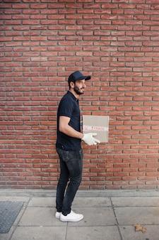 Seitenansicht eines lieferers mit paket vor brickwall