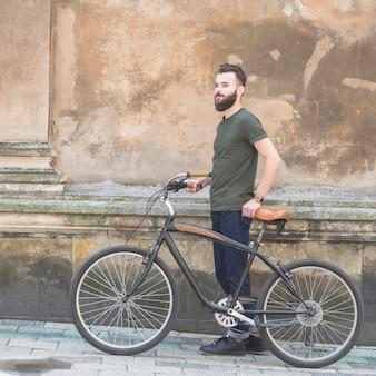Seitenansicht eines Mannes, der mit seinem Fahrrad vor alter Wand steht