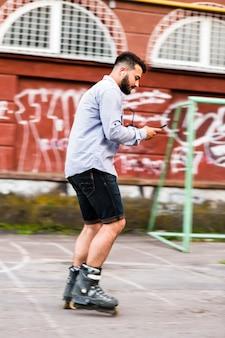 Seitenansicht eines mannes, der mobiltelefon während rollschuhlaufen im rochenpark verwendet