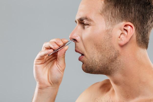 Seitenansicht eines mannes, der nasenhaare mit einer pinzette entfernt, die auf der grauen wand isoliert ist?