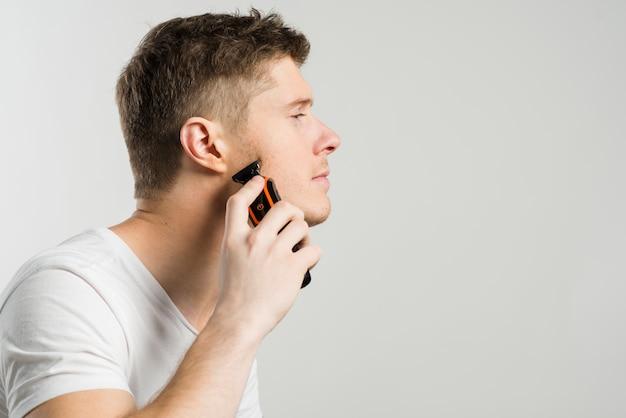 Seitenansicht eines mannes, der stoppeln mit einem elektrorasierer lokalisiert über grauem hintergrund rasiert