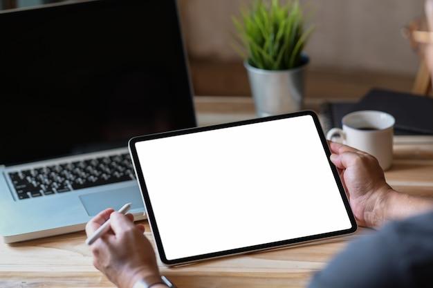 Seitenansicht eines mannes, der tablette in einem conner-büro hält