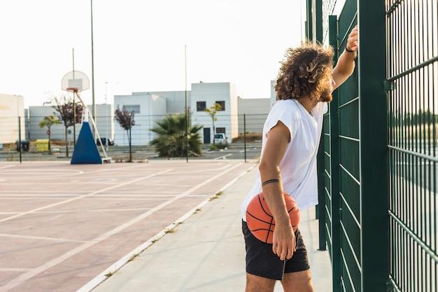 Seitenansicht eines mannes mit dem basketball, der durch zaun schaut