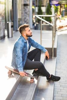 Seitenansicht eines mannes mit dem skateboard, das auf treppenhaus sitzt
