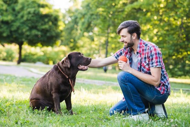 Seitenansicht eines mannes mit seinem hund auf gras