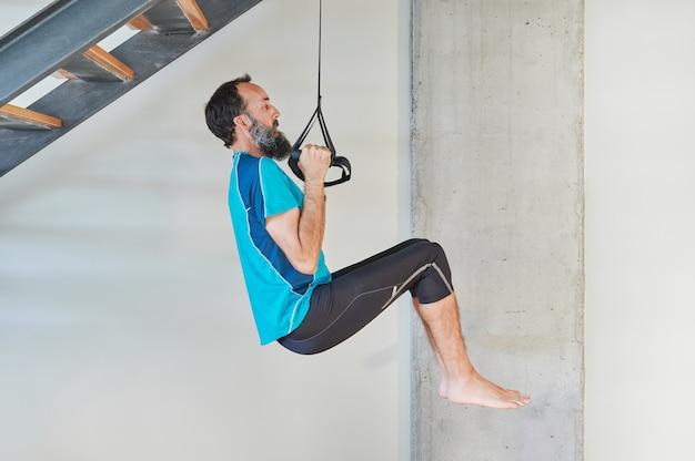 Seitenansicht eines mannes mittleren alters, der klimmzüge auf der treppe seines hauses macht