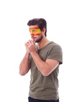 Seitenansicht eines nervösen fächers mit spanien-flagge im gesicht, das betet