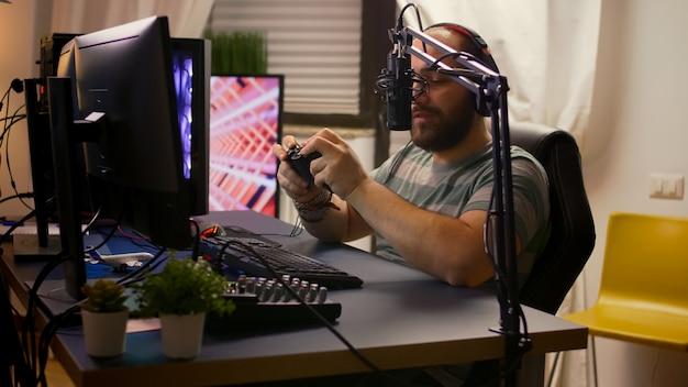 Seitenansicht eines pro-streamer-mannes mit kopfhörern, der online-videospiele mit geöffnetem streaming-chat spielt