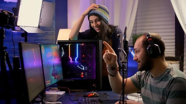 Seitenansicht eines pro-streamer-paares, das online-videospiele mit einem leistungsstarken computer mit mehreren monitoren durchführt